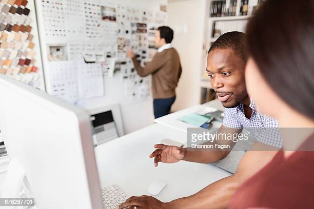 Designers reviewing ideas on desktop computer