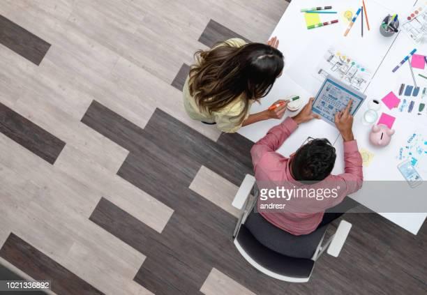 designers sharing ideas at a creative office - marketing foto e immagini stock