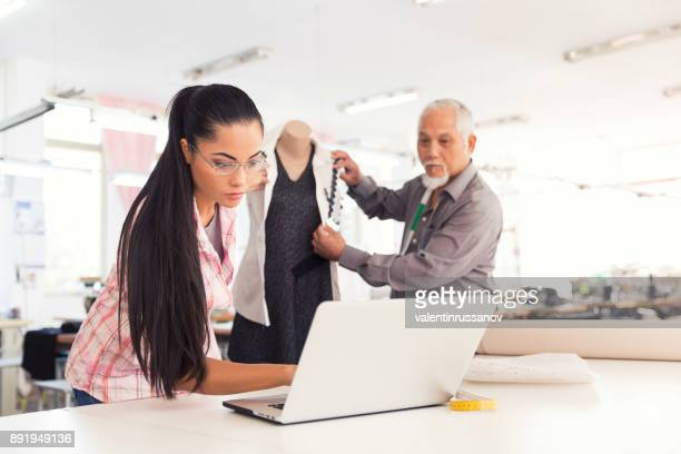 Designers using laptop in fashion studio
