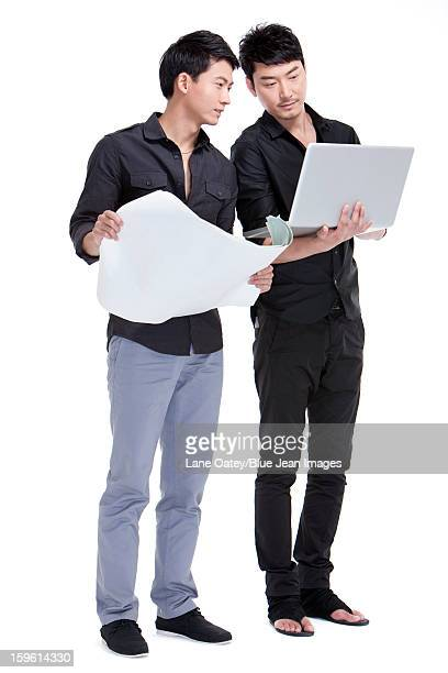 Designers with laptop and blueprint