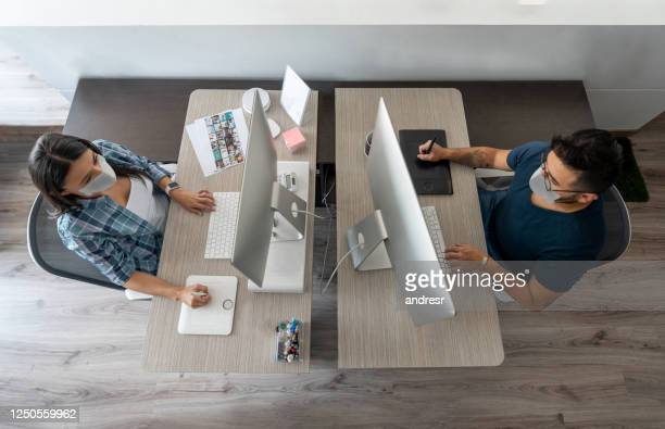 designers working at a creative office wearing a facemask and complying to social distancing - biosecurity stock pictures, royalty-free photos & images