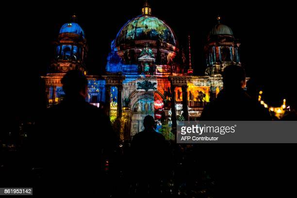 Designs are projected on the facade of the Berlin Cathedral on the last day of the yearly Festival of Lights in Berlin on October 15, 2017. / AFP...