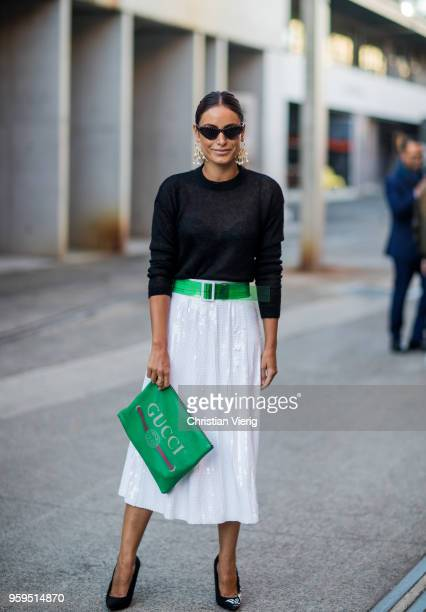 Desiree Deravi wearing white skirt green Gucci clutch Balenciaga heels earrings during MercedesBenz Fashion Week Resort 19 Collections at...