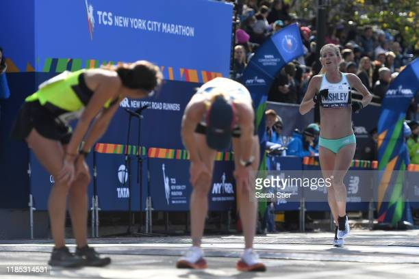 Desiree Linden of the United States catches her breath with Kellyn Taylor of the United States as Ellie Pashley of Australia crosses the finish line...