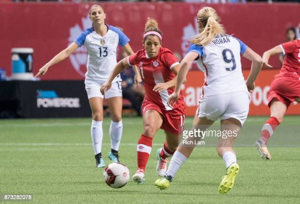 Desiree Scott of Canada tries to dribble the ball past Alex Morgan and Lindsey Horan of the United States during International Friendly soccer match...