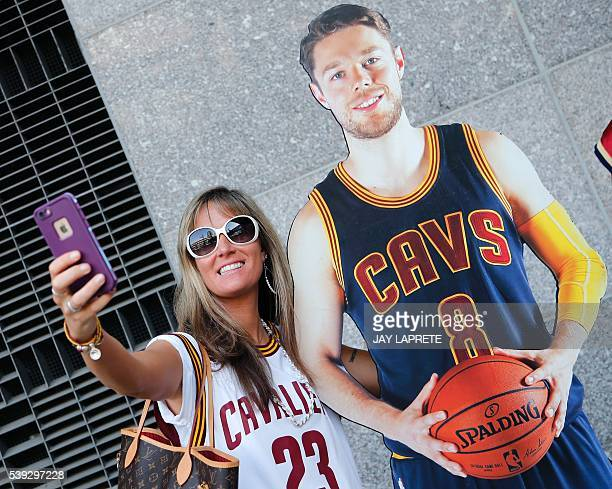 Desiree Shorey of Meadville Pennsylvania takes a selfie with a cardboard cutout of Cleveland Cavaliers guard Matthew Dellavedova before the start of...