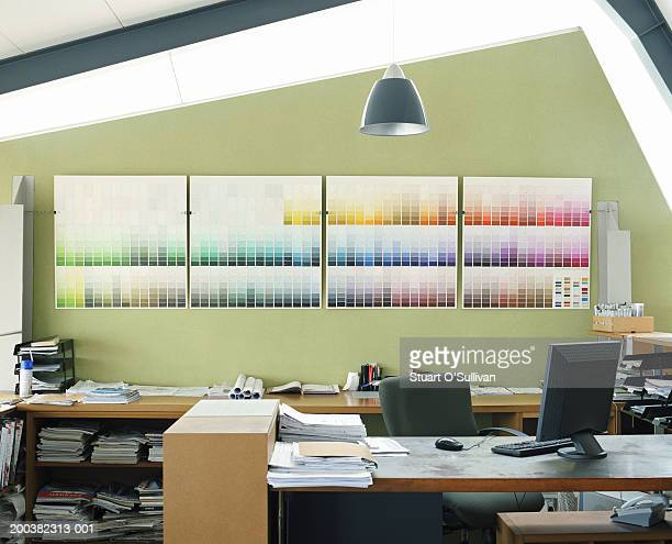 Desk area in office, colour charts on wall in background