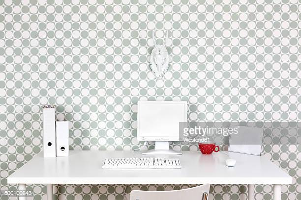 Desk at home office with white accessories in front of patterned wallpaper