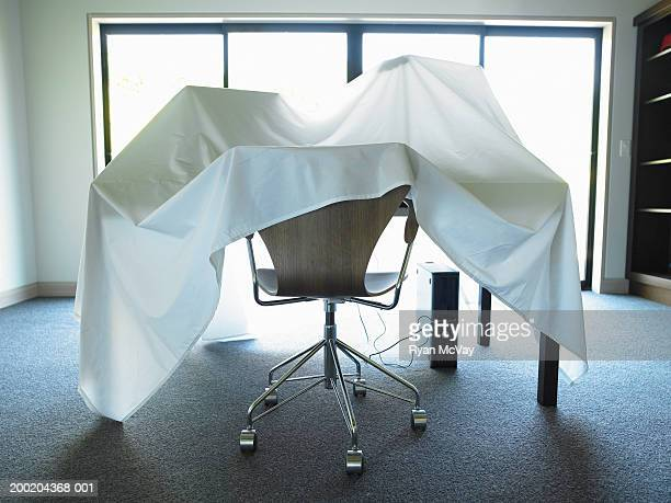 Desk, chair and computer covered with sheet