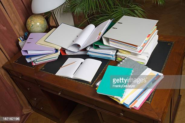 Desk, cluttered with binders and paper