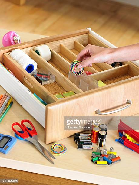 Desk drawer placed on wooden surface, hand putting rubber bands in compartment, surrounded by various other items of office stationery