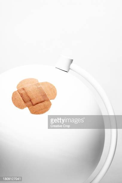 a desk globe has a sticking plaster stuck over a wound - microzoa stock pictures, royalty-free photos & images