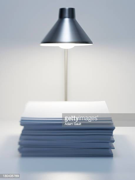 Desk lamp over stack of paper