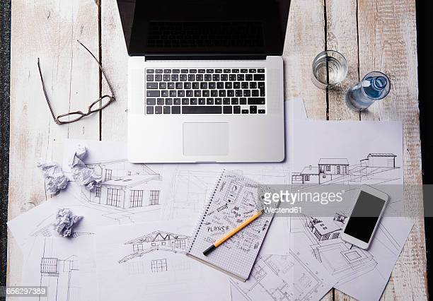Desk of an architect with laptop and sketches