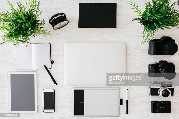 Desk of photographer with notebook, laptop, cameras, tablet and graphics tablet