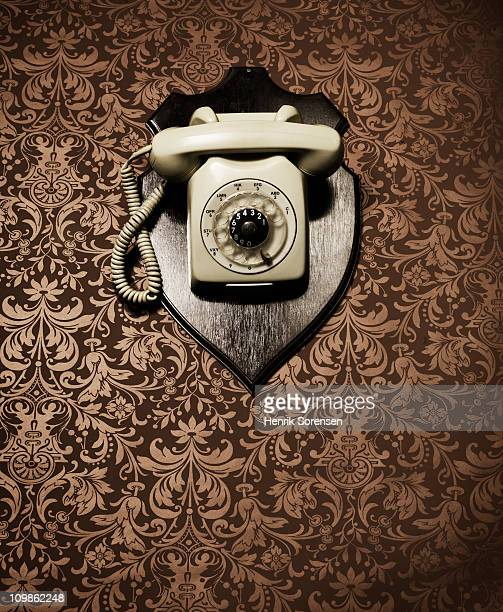 Desk telephone hanging as a trophy on a wall
