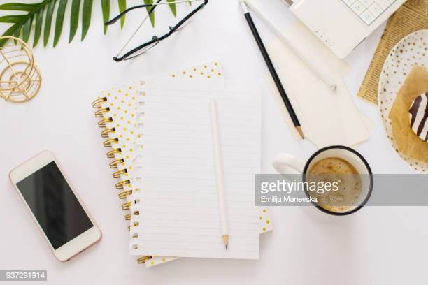 desk view with a blank notepad, open laptop, coffee and donuts - knolling concept stock pictures, royalty-free photos & images