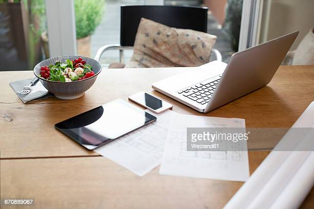 Desk with laptop and cell phone next to construction plan and salad