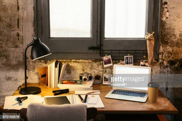 desk with laptop in a loft - belongings stock photos and pictures