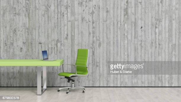 desk with laptop in front of concrete wall