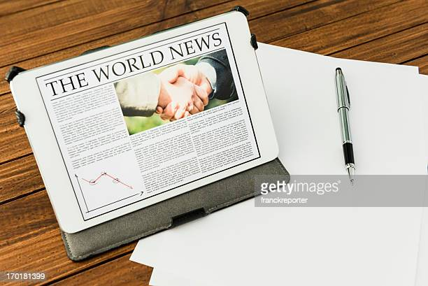 Desk with World news on digital tablet - New york