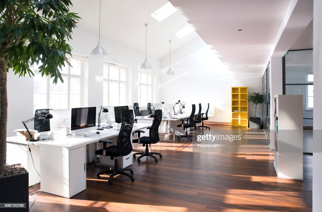 Desks with PCs in bright and modern open space office : Stockfoto