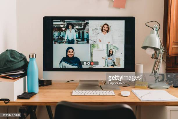 desktop pc with four people having a meeting at distance - video still stock pictures, royalty-free photos & images