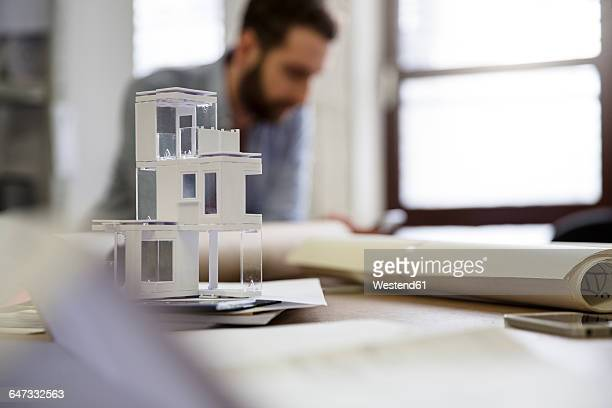 Desktop with architectural model and man in background