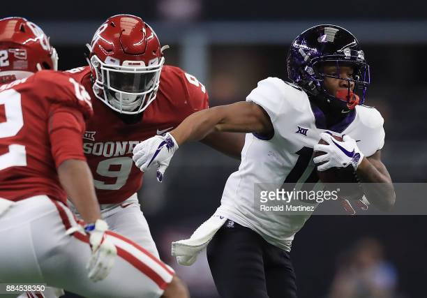 Desmon White of the TCU Horned Frogs runs the ball against Kenneth Murray and Will Johnson of the Oklahoma Sooners in the second quarter during Big...