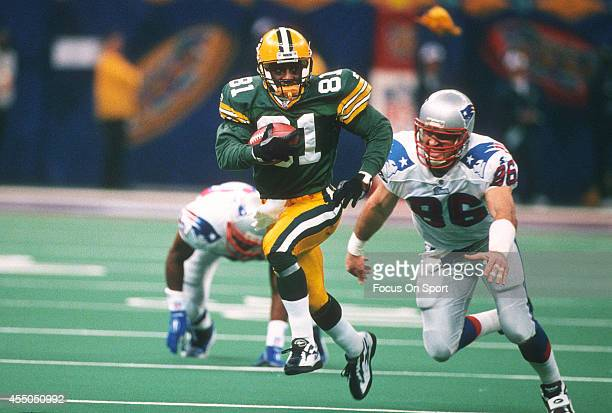 Desmond Howard of the Green Bay Packers returns a kickoff while pursued by Mike Bartrum of the New England Patriots during Super Bowl XXXI January 26...
