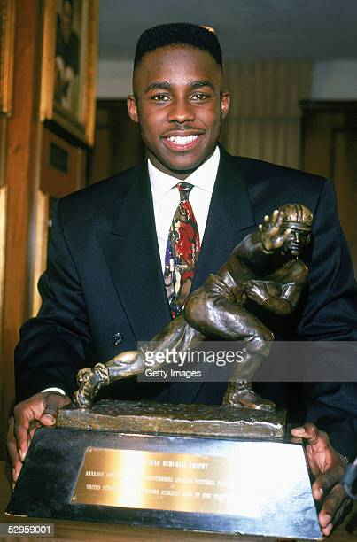 Desmond Howard of the Michigan Wolverines poses after being awarded the Heisman Trophy given to the top player in the National Collegiate Athletic...
