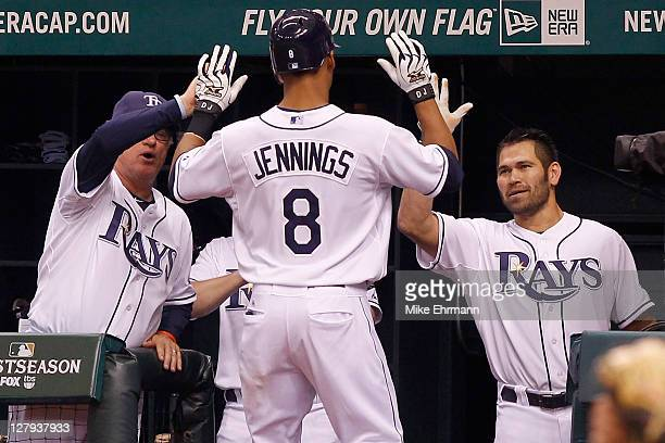 Desmond Jennings of the Tampa Bay Rays heads back to the dugout and celebrates with manager Joe Maddon and Johnny Damon after Jennings hits a solo...