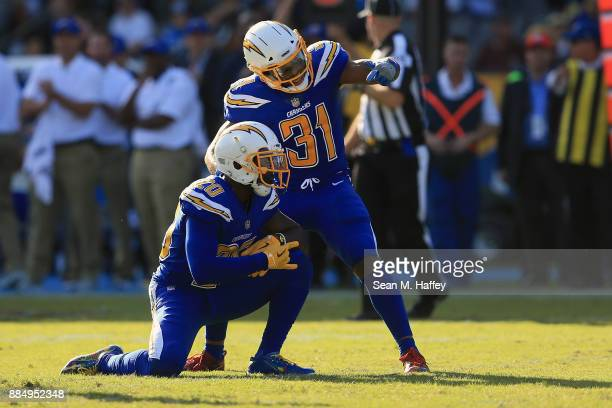 Desmond King and Adrian Phillips of the Los Angeles Chargers react after DeShone Kizer of the Cleveland Browns is sacked during the second quarter of...