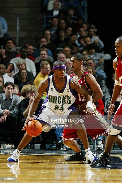Desmond Mason of the Milwaukee Bucks is defended by Kevin Ollie of the Cleveland Cavaliers during the game at Bradley Center on January 30 2004 in...