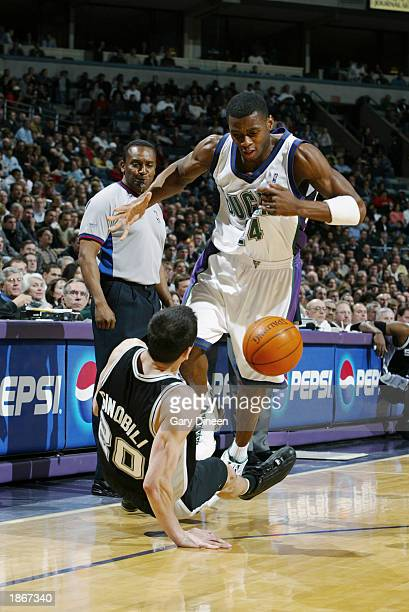 Desmond Mason of the Milwaukee Bucks knocks over Emanuel Ginobili of the San Antonio Spurs during the game at Bradley Center on March 11 2003 in...