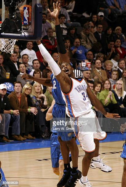 Desmond Mason of the Oklahoma City Thunder lays the ball up while being guarded by Dwight Howard of the Orlando Magic at the Ford Center November 12...