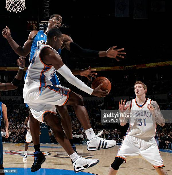 Desmond Mason of the Oklahoma City Thunder tries passing the ball to teammate Robert Swift while being guarded by Dwight Howard of the Orlando Magic...