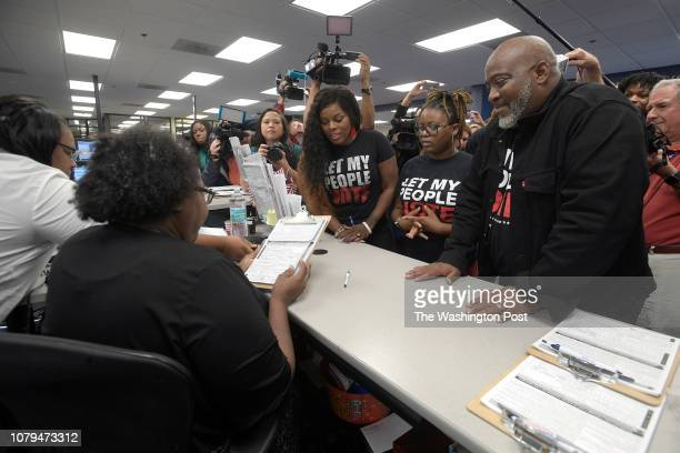 Desmond Meade right is accompanied by his daughter Xcellence Meade center and his wife Sheena Meade inside the Orange County Supervisor of Elections...