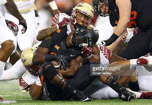 Desmond Roland of the Oklahoma State Cowboys is tackled by the Florida State Seminoles defense in the first half of the Advocare Cowboys Classic at...