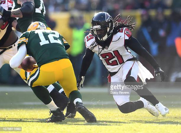 Desmond Trufant of the Atlanta Falcons sacks Aaron Rodgers of the Green Bay Packers during the first half of a game at Lambeau Field on December 09...