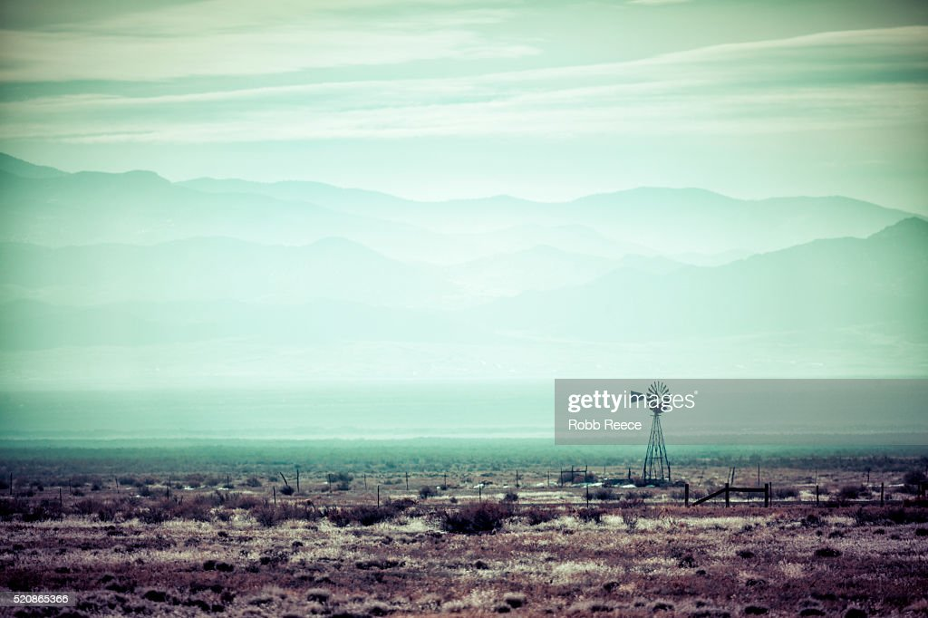 Desolate, desert landscape with old windmill : Stock Photo
