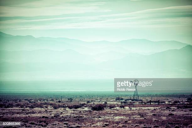 desolate, desert landscape with old windmill - robb reece stock photos and pictures