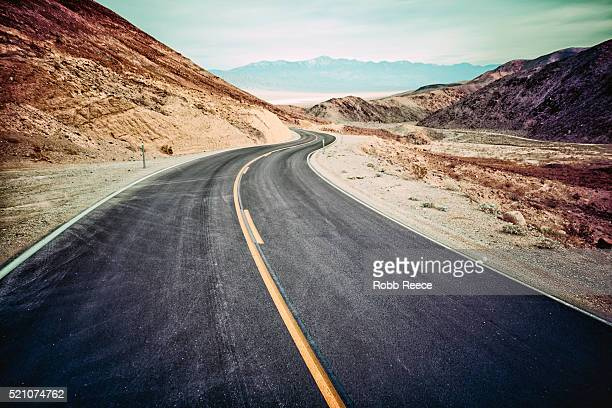 a desolate, winding, paved highway in death valley, ca - robb reece stock-fotos und bilder