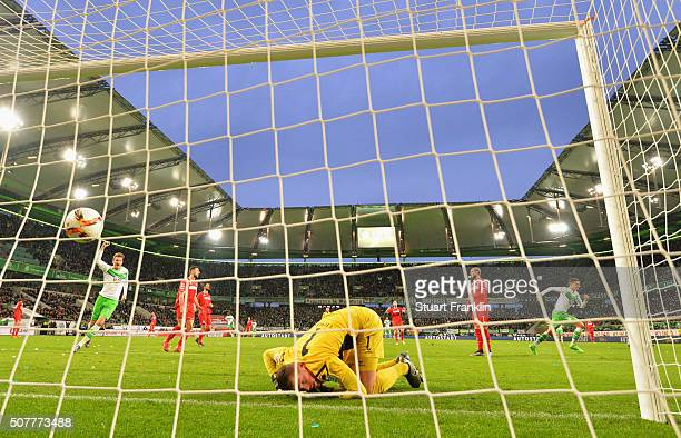Despair for goalkeeper Timo Horn of Cologne as Julian Draxler of VfL Wolfsburg celebrates as he scores their first goal during the Bundesliga match...