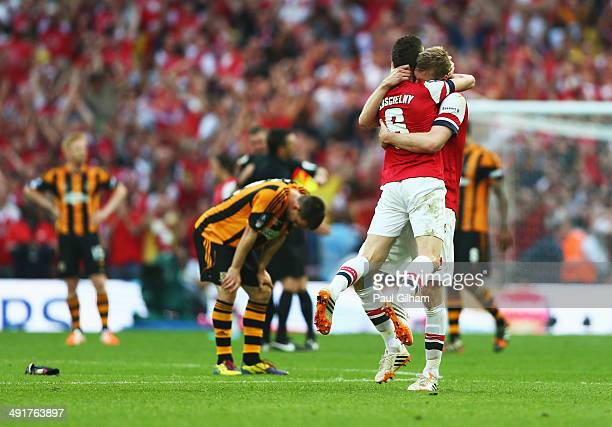 Despair for Hull City as Laurent Koscielny and Per Mertesacker of Arsenal celebrate victory after the FA Cup with Budweiser Final match between...