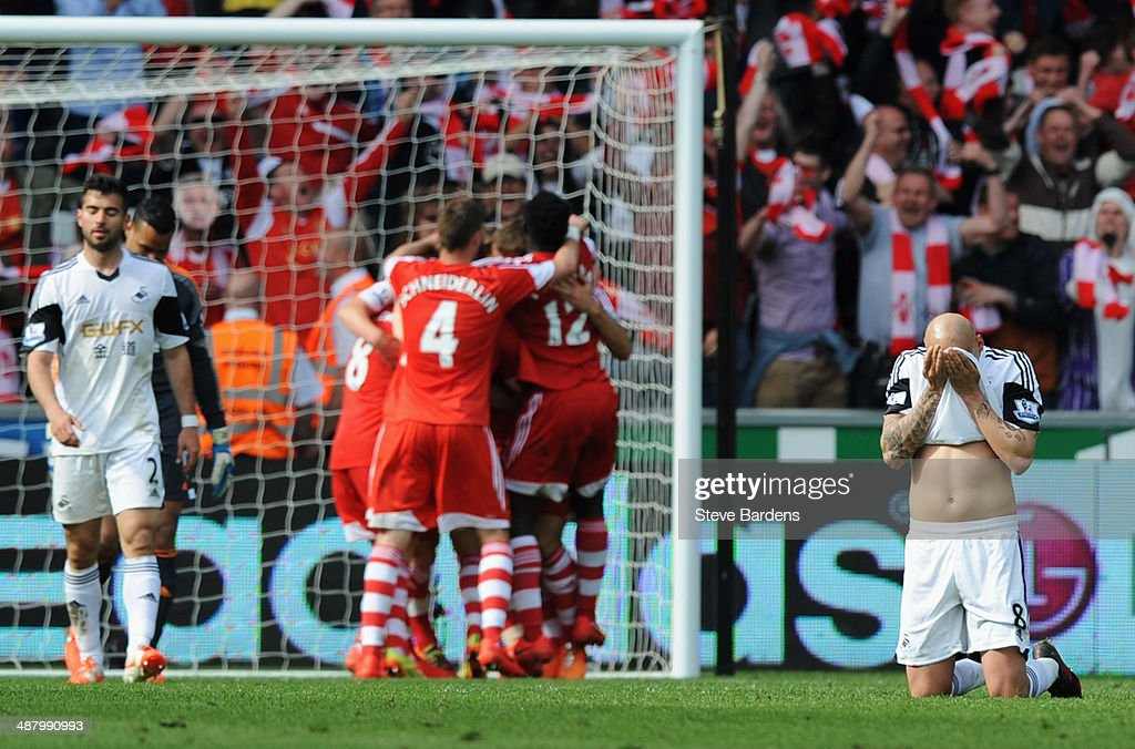 Despair for Jonjo Shelvey of Swansea City (R) as Rickie Lambert of Southampton is congratulated by team mates as he scores their first goal during the Barclays Premier League match between Swansea City and Southampton at Liberty Stadium on May 3, 2014 in Swansea, Wales.