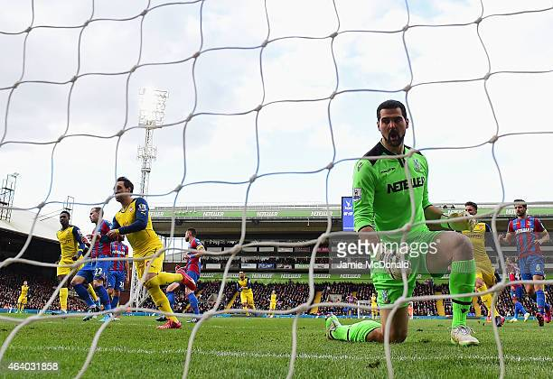 Despair for Julian Speroni of Crystal Palace as Santi Cazorla of Arsenal celebrates as he scores their first goal from a penalty during the Barclays...