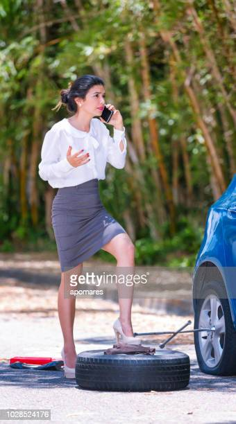 despair hispanic young business woman calling for assistance on the road due to flat tire - flat tire stock pictures, royalty-free photos & images