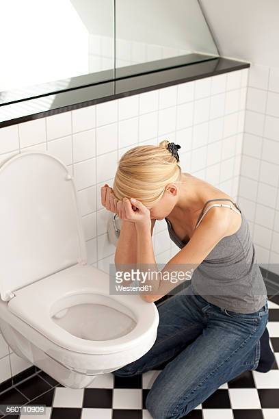 despaired anorexic young woman at the toilet - bulimia stock photos and pictures