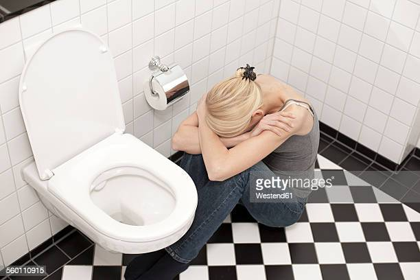 despaired anorexic young woman at the toilet - bulimia fotografías e imágenes de stock
